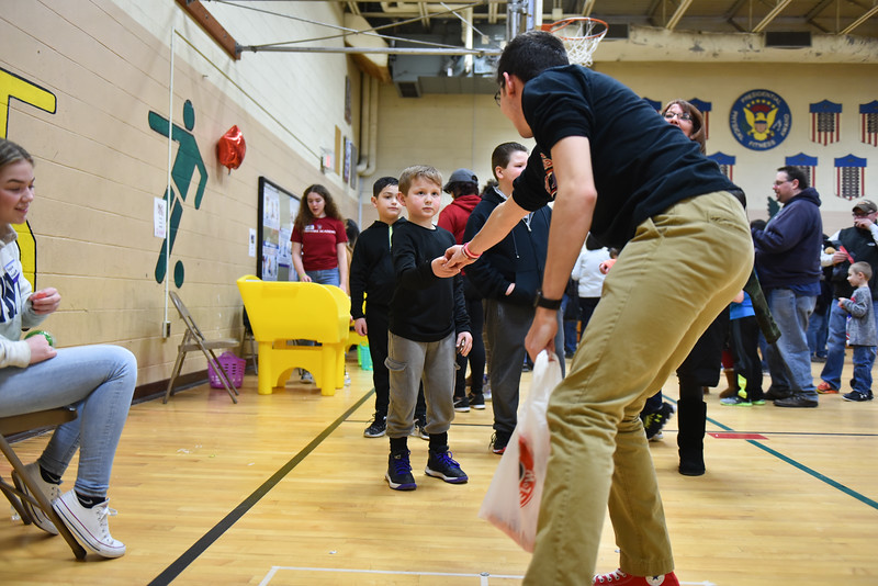 Fitchburg High School junior Ethan Aubuchon hands Braiden Robichaud, 8, a prize at the annual Bunny Breakfast on Saturday at Reingold Elementary School in Fitchburg.  SENTINEL & ENTERPRISE JEFF PORTER