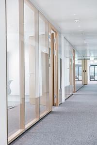24 Das neue Managementgebäude: durch die innenräumliche Umstrukturierung konnten die Zellenbüros zu transparenten, Open Office Bereichen umgestaltet werden. | The new management building: the redesign of the interior layout transformed seperate offices into transparent, open office areas.