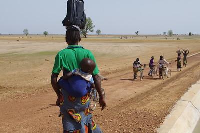 Femme et son enfant allant aux champs