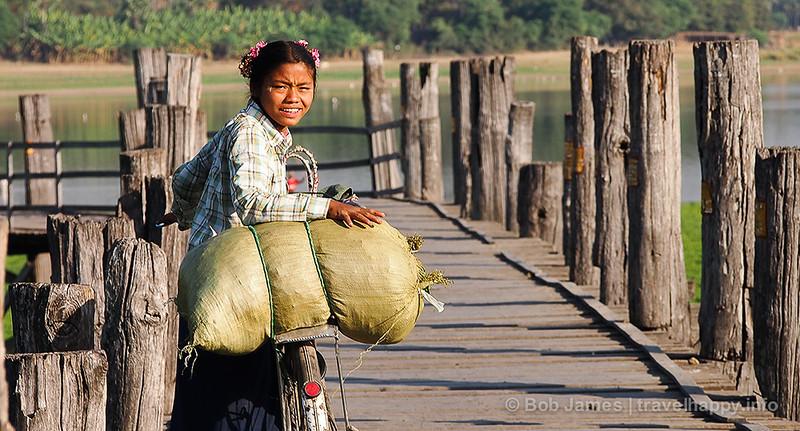 A Burmese schoolgirl looks back for a friend as she walks her bicycle across Amarapura's U Bein Bridge