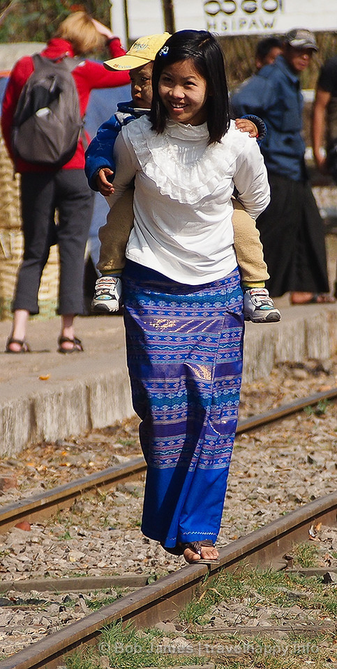 A mother tries to keep her balance to entertain her boy as they wait for the train in Hsipaw