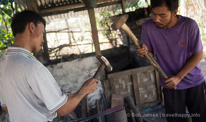 Two blacksmiths pound out a tool in the Shan village on the northern edge of Hsipaw