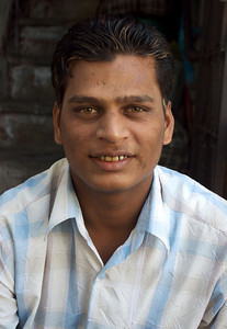 His teeth are colored from the tobacco (or tobacco-like) substance that they chew.