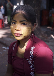 The yellow paint on her face is natural sunscreen, used mostly by women and children.
