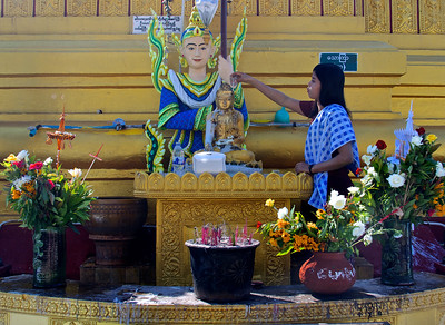 Woman Pouring Water Over Buddha Statue
