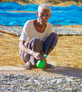 Man Spraying Dried Fish