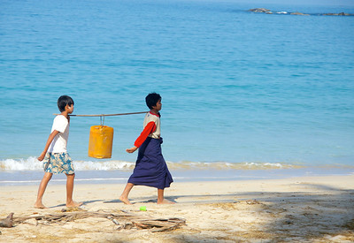 Boys Carrying Water Along the Beach