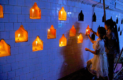 Mother and Daughter Lighting Candles on Exterior Wall
