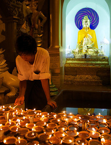 Man Lighting a Candle Near Buddha Shrine