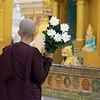 Monk With Flowers Outside A Shrine<br /> Shwedagon Pagoda<br /> <br /> Yangon, Burma<br /> 29 July 2012