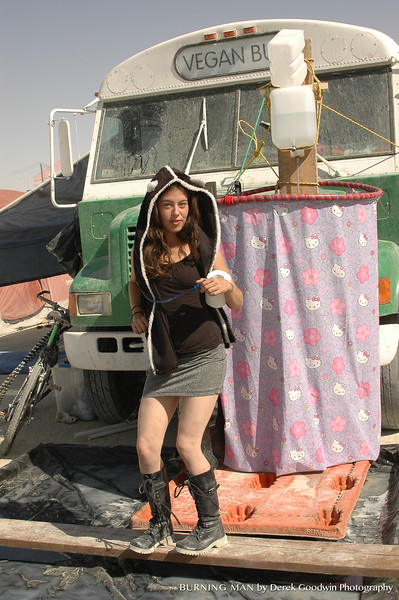 Megan LaBonte in front of the Vegan Bus posing next to our hula hoop shower - using a solar shower hanging off the bus and shower curtains suspended by a hula hoop.
