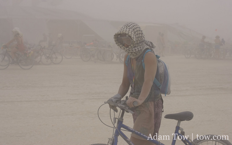 Rae does not look happy walking her bike back to camp during the dust storm