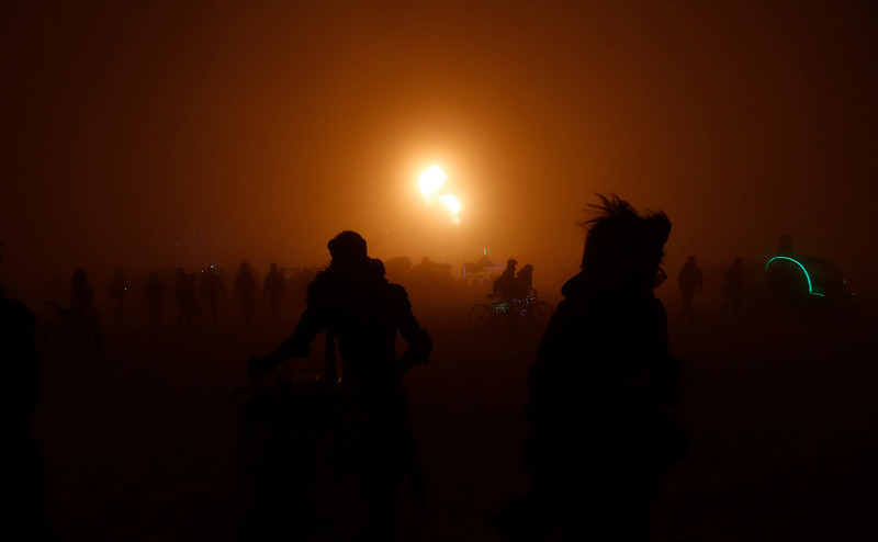 Participants walk across the playa in the glow of a flame during the annual Burning Man festival in Black Rock Desert, Nev. on Sept. 3, 2016.