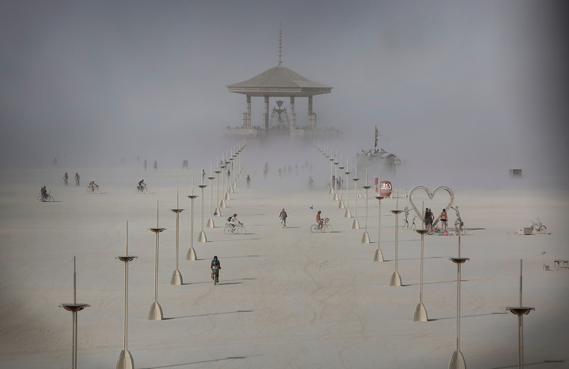 Participants walk across the playa as a dust storm approaches the Man as approximately 70,000 people from all over the world gathered for the annual Burning Man arts and music festival in Black Rock Desert, Nev. on Aug. 30, 2017.