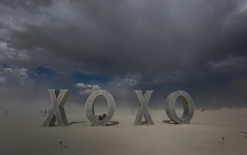 A participant sits on an art structure during the annual Burning Man festival in Black Rock Desert, Nev. on Aug. 30, 2017.