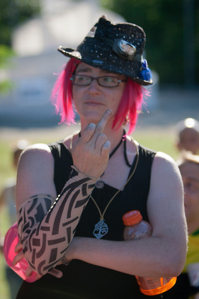 Kay wears pink hair, a tat-sleeve and one of Q's dresses while affecting a decent impression of someone from North Dakota