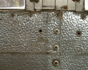 Rivets along the bottoms and sides of the sheet metal panels, spot (or tack?) welds along the top.