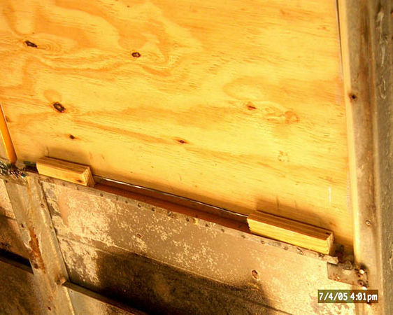 The plywood is held in place with shims of scrap plywood wedged along the lower and upper frame