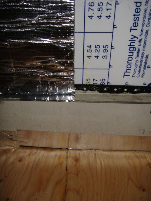 "The bottom edge of the insulation is foil-taped to the rail.  (The rail protrudes about 1.25"" from the wall.  It is part of the same piece of metal that forms the floor.  This rail supported the outboard side of the school bus seats.)<br /> <br /> The vapor barrier on the floor (under the plywood) has been trimmed and foil-taped to the wall."