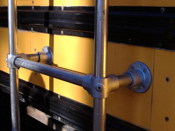 The side rails are continuous 6.5' sections of pipe. Near the bottom we added a 3-outlet fitting and a flange to the side of the bus.