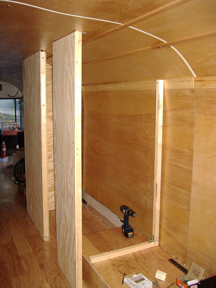 "Partially complete rear bathroom enclosure.  The entryway to the bathroom is 18"" wide and the ceiling is just under 6'.  The wood-burning stove will be located on the wheel well, just aft of the rear bathroom wall.  We found a <a href=""http://www.fatscostoves.com/"" target=""_new"">Fatsco</a> Tiny-Tot marine solid-fuel stove on ebay that seems to be the right size for the job."