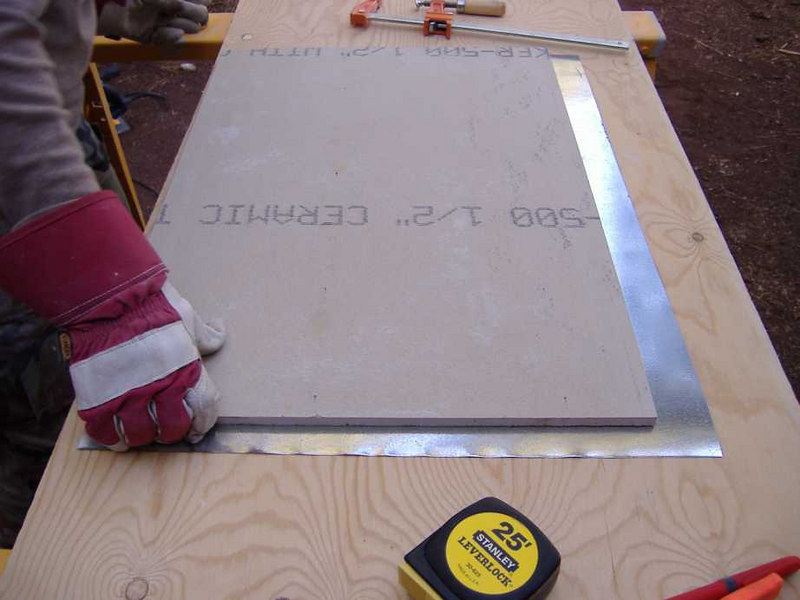 "We began by cutting 1/2"" cement board to size, and followed by cutting 26ga sheet steel oversized by about an inch.  The extra metal allows us to bend the edges to fold over the sides of the cement board for a more finished appearance."