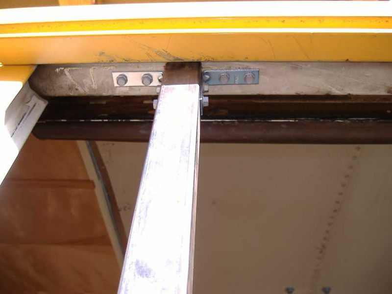 Upper end of vertical frame member, secured by angle brackets and self-drilling screws.