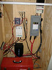 Electrical center.  Included are:<br /> MorningStar Tri-Star TS-45 solar charge controller (upper right)<br /> Square-D fused safety disconnect (grey box below charge controller)<br /> Exceltech pure sine wave inverter (black box @ bottom)<br /> Xantrex DC Load controller (white box above inverter)<br /> Trimetric 2020 system monitor (above load controller)<br /> <br /> Also visible are the common negative buss (above Trimetric) and power distribution point (to the right of Trimetric).<br /> <br /> One the wall to the left, at the bottom is the backside of the DC fuse/switch panel.  Way above that is the rear of one of the Polk Momo MMC460 speakers.