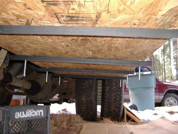 "We muscled the tank and bottom layer of OSB back into position -- everything fits perfectly!<br /> <br /> The 1"" angle iron supports were painted with rust-inhibiting enamel before being attached.<br /> <br /> <br /> When full, the 58-gallon tank will weigh roughly 500 pounds. Eight support points means 62.5 pounds per...which seems to be a safe load."