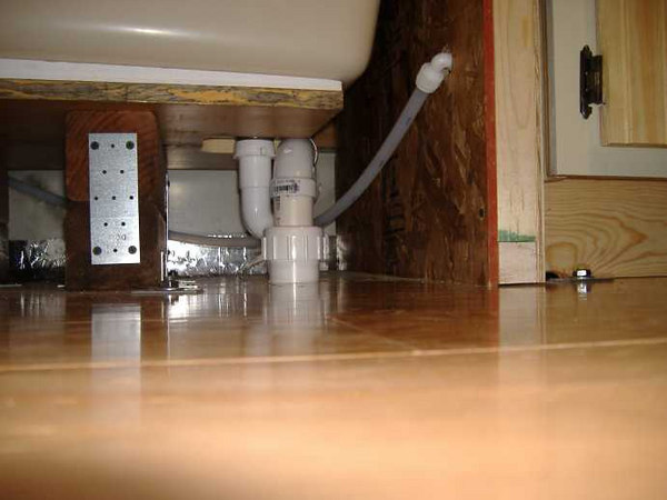 The shower drain with trap and union.  <br /> <br /> Also present is the freshwater supply line -- to the right is the kitchen counter unit.
