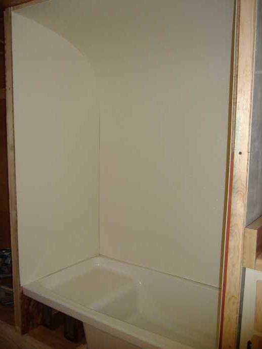 A little work with a sander and the rear FRP panel fits pretty well.  There aren't any gaps that can't be caulked for water-tightness.<br /> We'll finish the front of the tub with a panel of plywood on a hinge so the plumbing can be accessed if needed.