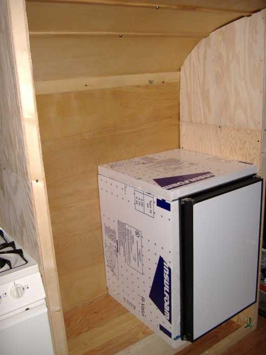 "A dry-fit of the fridge and insulation (2"" foam).  This will determine the location of the dividing wall as well as the shelf above the fridge opening.  The <a href=""http://www.novakool.com/index.htm"">Nova Kool</a> R4500 has an internal volume of 4.3 cubic feet and draws 2.2 amps at 12 volts DC.  For comparison...a compact fridge from Sears uses 315 kilowatt-hours per year, or 863 watts per day...which at 120 volts is 7.191 amp-hours.  The Nova Kool uses 2.2 amps at 12 volts DC, which is .22 amps at 120 volts AC.  <strong>This means the Nova Kool would have to run continuously more than 32 hours per day to use the same electricity used by the Sears model.</strong>  On average, fridges run 25% - 35% (6 - 8.5 hours) of the day, depending on ambient external temperatures and other factors.  We opted against a propane model because of the requirement to have the vehicle within 3% of level.  We also didn't want to deal with adding an exhaust vent stack.  We also considered 12vdc refrigerator models by <a href=""http://www.waecousa.com/"">Waeco</a>, <a href=""http://www.norcold.com/norcold_home.cfm"">Norcold</a>, <a href=""http://www.sundanzer.com/"">SunDanzer</a>, and Zero."