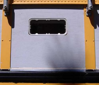 After cutting the hole, the window is inserted from the inside.  The edge of the spigot is flush with the outside wall of the bus.
