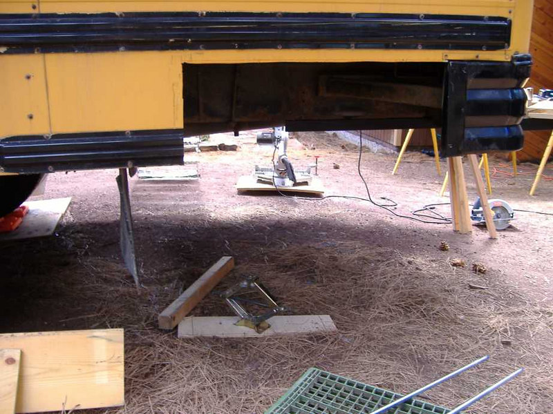 First step is to cut a gaping hole in the side skirting of the bus.  This is the rear on the driver's side.  We chose this location because the propane appliances are on this side of the bus, and this is the largest (and most easily accessed) available underbody space.