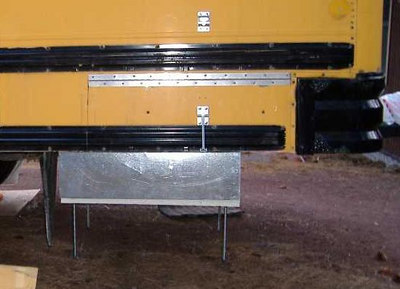 """The hinge was then screwed to the bus body.<br /> <br /> The tank hangs about 8"""" below the bottom of the bus body, so we used (again, leftover) 26 GA sheet metal to cover it.<br /> <br /> A door holder has been added."""
