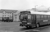 Leyland National B49F 718 (PEV 690R) and a Mercedes L608D minibus pictured on a damp day at Porthcawl.