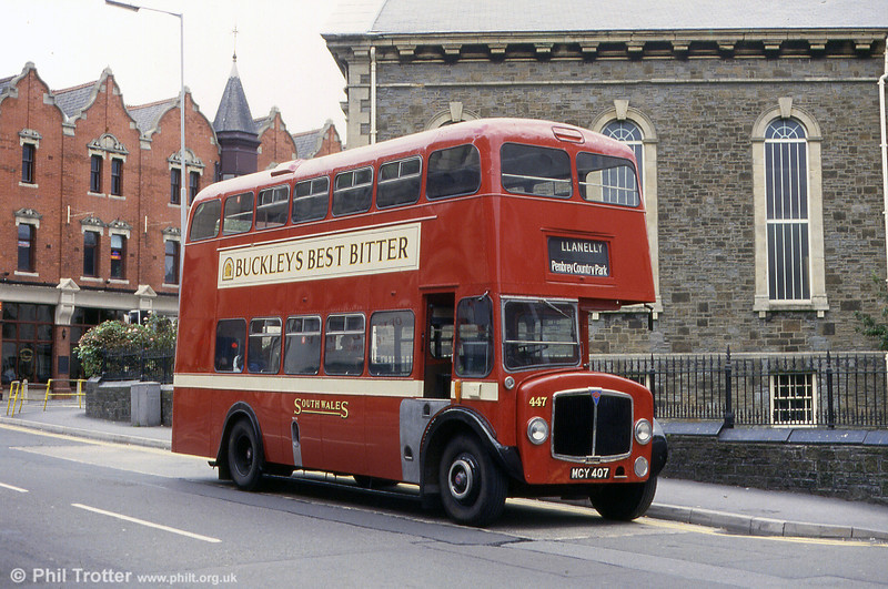 <DIV ALIGN=left>Of the many AEC bus designs which operated in this area, the '400s' are well remembered. The name refers to a batch of AEC Regent Mark Five double deckers numbered in the 400 series and whose most distinctive trademark was the growling AV470 engine, often heard several streets away! Perhaps they weren't really that loud; there was less traffic in those days... The buses first came into the SWT fleet in 1955 with deliveries continuing until 1957. The earliest examples were amongst the first production Regent Mk.Vs, carrying chassis numbers 003 upwards, underlining SWT's willingness to purchase new designs.  There were three basic varieties of 'Four Hundreds'; normal height with Weymann bodywork, normal height with Willowbrook bodywork and the low height Weymann design. All had their entrances at the rear. The first deliveries were the normal height Weymann type (numbered 440 to 449, MCY 400-409), looking very smart in their deep red and cream livery. Indeed, the type was the last to carry the cream waistband which was a feature of the 1960s fleet. The earliest examples were allocated to Llanelli and some had platform doors at the rear - unusual in the SWT fleet and reportedly for use on the Llanelli to Swansea service 2.  Recreating the past: Preserved 1955 AEC Regent V/Weymann H33/26RD 447 (MCY 407) in Station Road, Llanelli.</DIV>