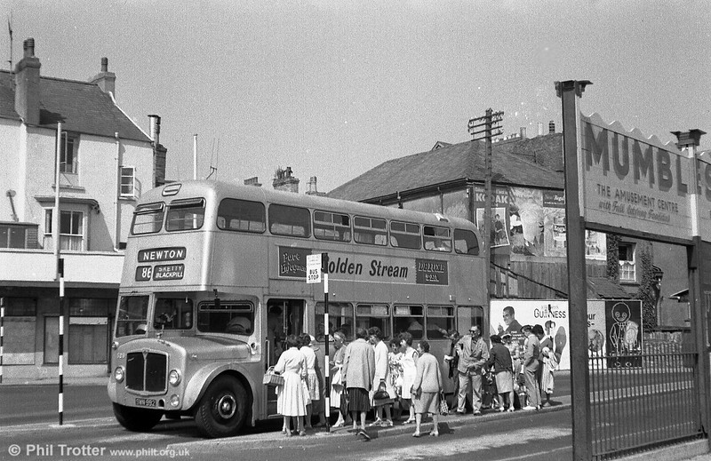 <DIV ALIGN=left>AEC Regent V/Weymann H39/32F 529 (SWN 992) is seen loading up with shoppers at Oystermouth. In the long term, the silver buses proved to be a false economy. While the unpainted vehicles offered certain cost advantages at the time of delivery, ongoing cleaning and maintenance costs were often higher. This was because small dents and scrapes which, on a red bus could simply be filled and painted, on an unpainted one involved totally replacing one or more body panels. A bus which had received several repairs would take on a patchwork appearance!</DIV>