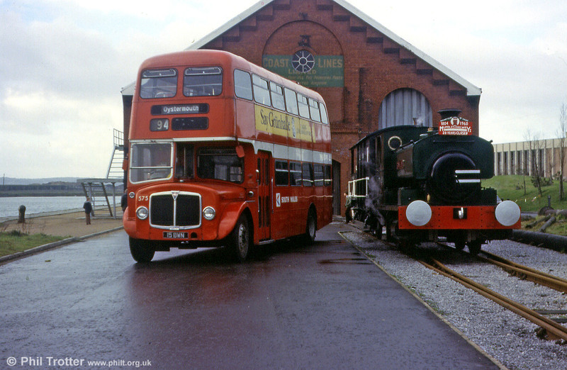AEC Regent V/Willowbrook H39/32F 575 (15 BWN) poses alongside the Railway Club of Wales locomotive 'Rosyth No.1' (AB 1385/1914) at Swansea Maritime & Industrial Museum in 1980.