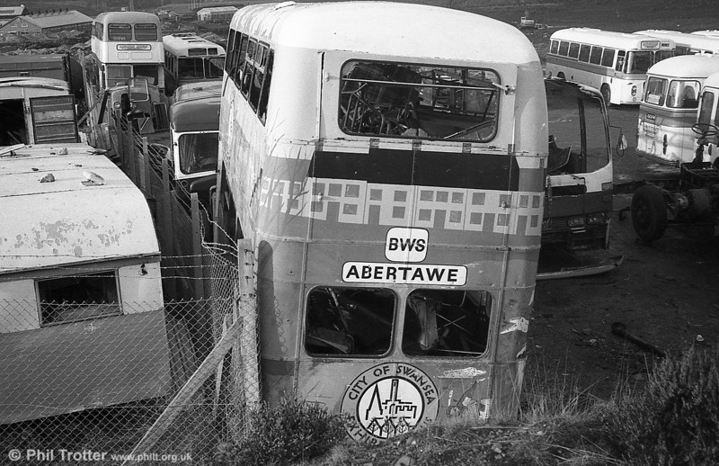 AEC Regent V/Willowbrook H39/32F 561 (996 BCY) at the premises of Morris Bros., Swansea. It had previously been used as a promotional vehicle by Swansea City Council. Sister 568 is in the background.