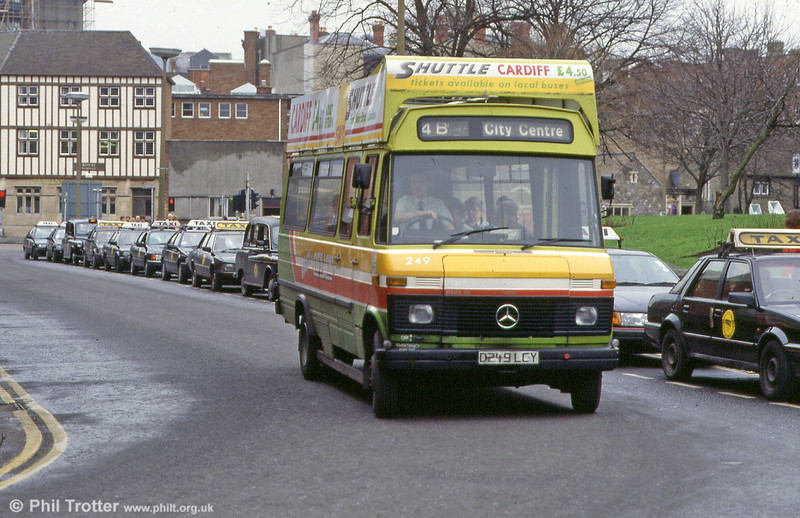 249, promoting the Swansea to Cardiff Shuttle service, passes a line of taxis at St. Mary's Square.