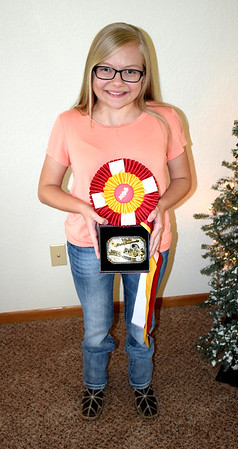Makenzie Bushue holds her prize ribbon and belt buckle she recently received for being placed Reserve World Champion in the Youth 3 and 4-year-old Halter Gelding class in Tulsa, Oklahoma. Bushue also won a championship jacket. Charles Mills photo