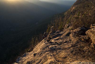 Sunbeams stream through the clifflines