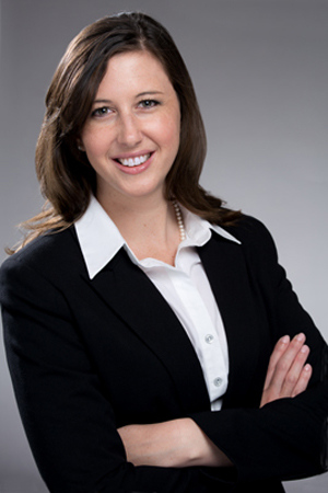 Executive headshot of young woman arms crossed