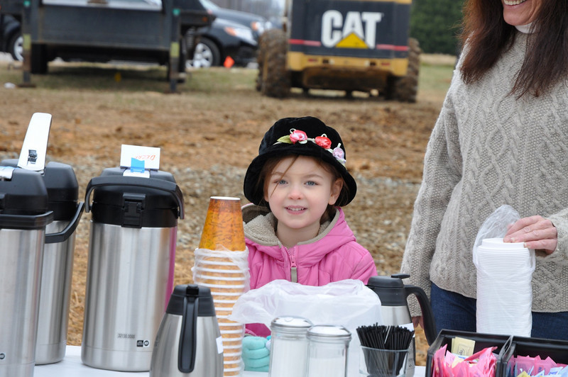 Ellie Fivas, 6, of Indian Trail keeps warm helping to serve hot coffee from Madisons.