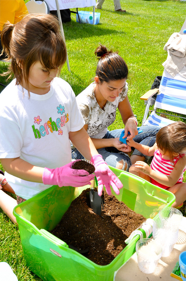 Mom prepares Ella Mroz,2, with gloves to plant flower seeds in dirt along with sister Abigail, 8, from Charlotte