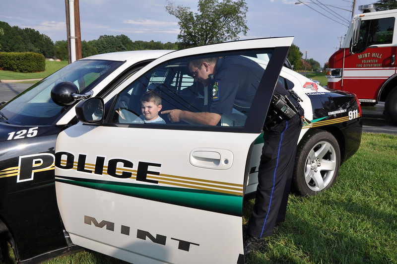 MHPD Officer Giman explains to Carter Swett, 4, MH, how the car computer works to help catch a bad guy.