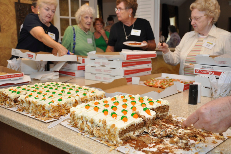 Neighborhood Watch Member Pat Shay serves up the pizza and carrot cake with Rachel Porter, Doris Reuter, Lillian Gourd.