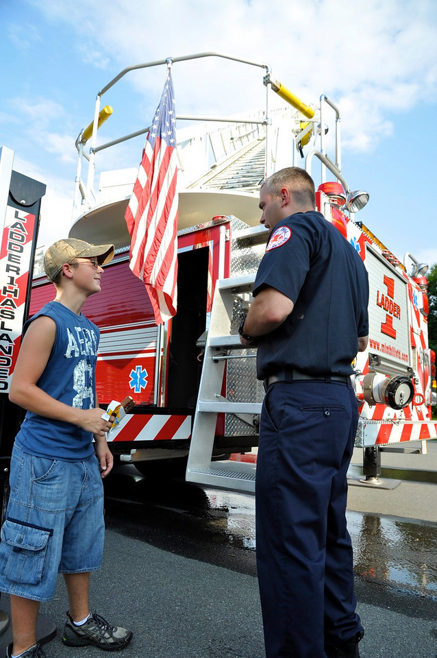 MH Firefighter extraordinaire (as he calls himself) Klotzer talks to Jonathon Beck,15, from Stanfield NC, about the workings of climbing up the truck's ladder.