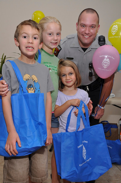 SPD Sgt.Cranford gives goody bags to Alex,7, Madison,10,Eliza,5-the Brook Family.